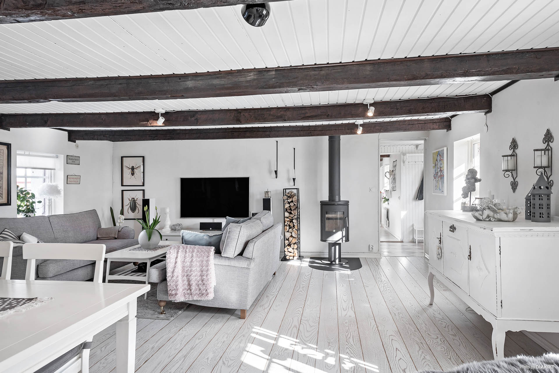 """Underbart vardagsrum med karaktär! Synliga bjälkar, ljust målade väggar och ett ekgolv """"white oak"""". Vi finner en värmande kamin och här finns plats för både soffan och matplatsen."""