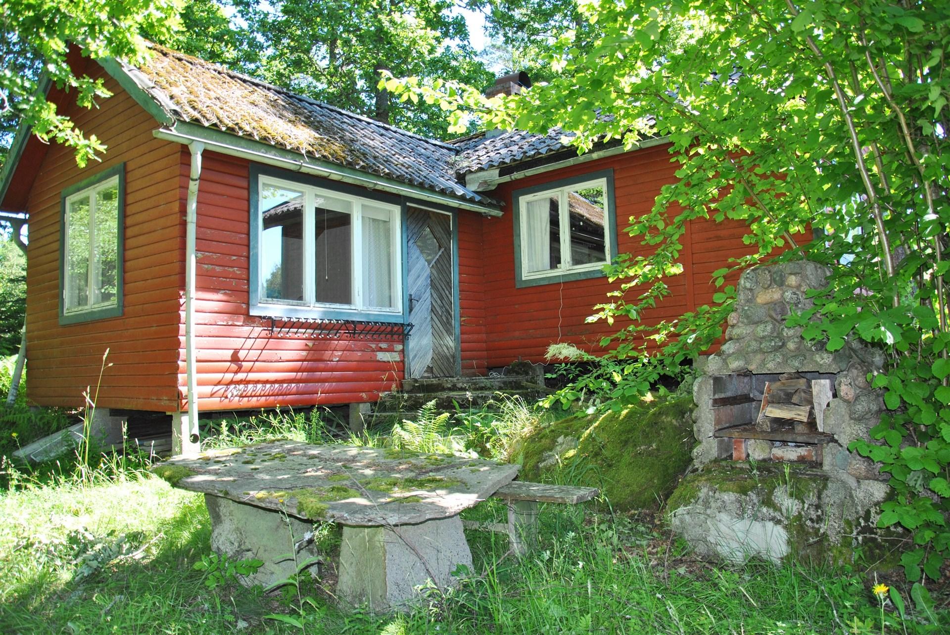 Huset ligger i vinkel (närmast delen som byggdes till på slutet av 70-talet). Notera stenbordet och utegrillen