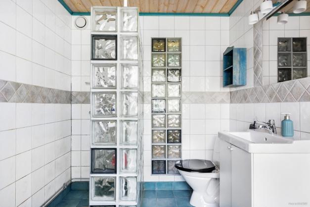 En suite badrum med duschhörn av glasbetong, toalett och kommod