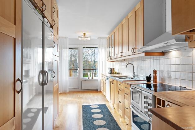 Kök med en modern planlösning i form av en stor öppning mot vardagsrummet.