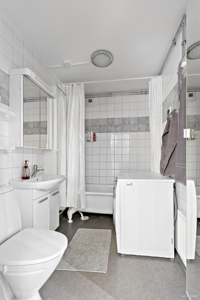 Fräscht badrum med badkar och tvättmaskin.