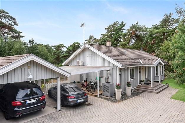 Dubbla carportar förbinder villan med gästhus och förråd.