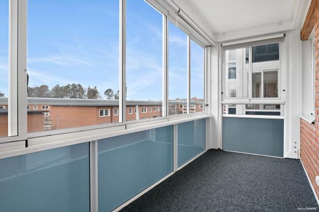 Rymlig balkong med skjutbara fönsterpartier.