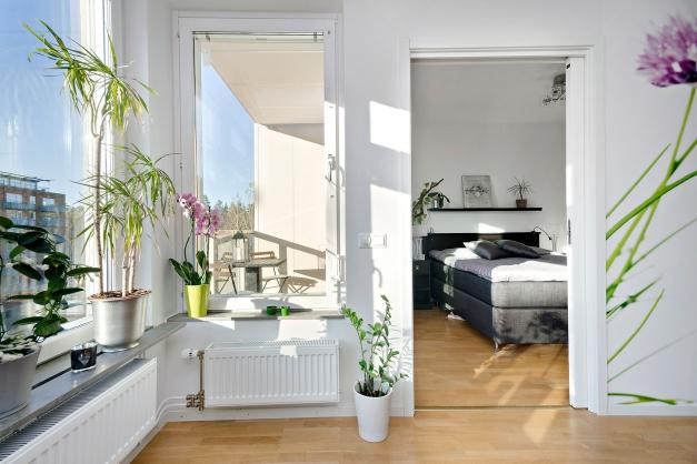 Ljust och luftigt vardagsrum med fönster i tre väderstreck