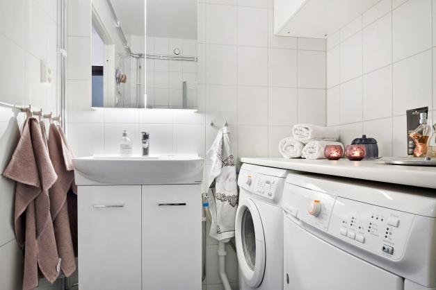 Fräscht helkaklat badrum med tvättmaskin och torktumlare.