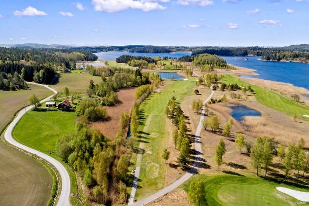 Tomten är 3.734 m² och till höger om vägen öppna, gröna ytan.