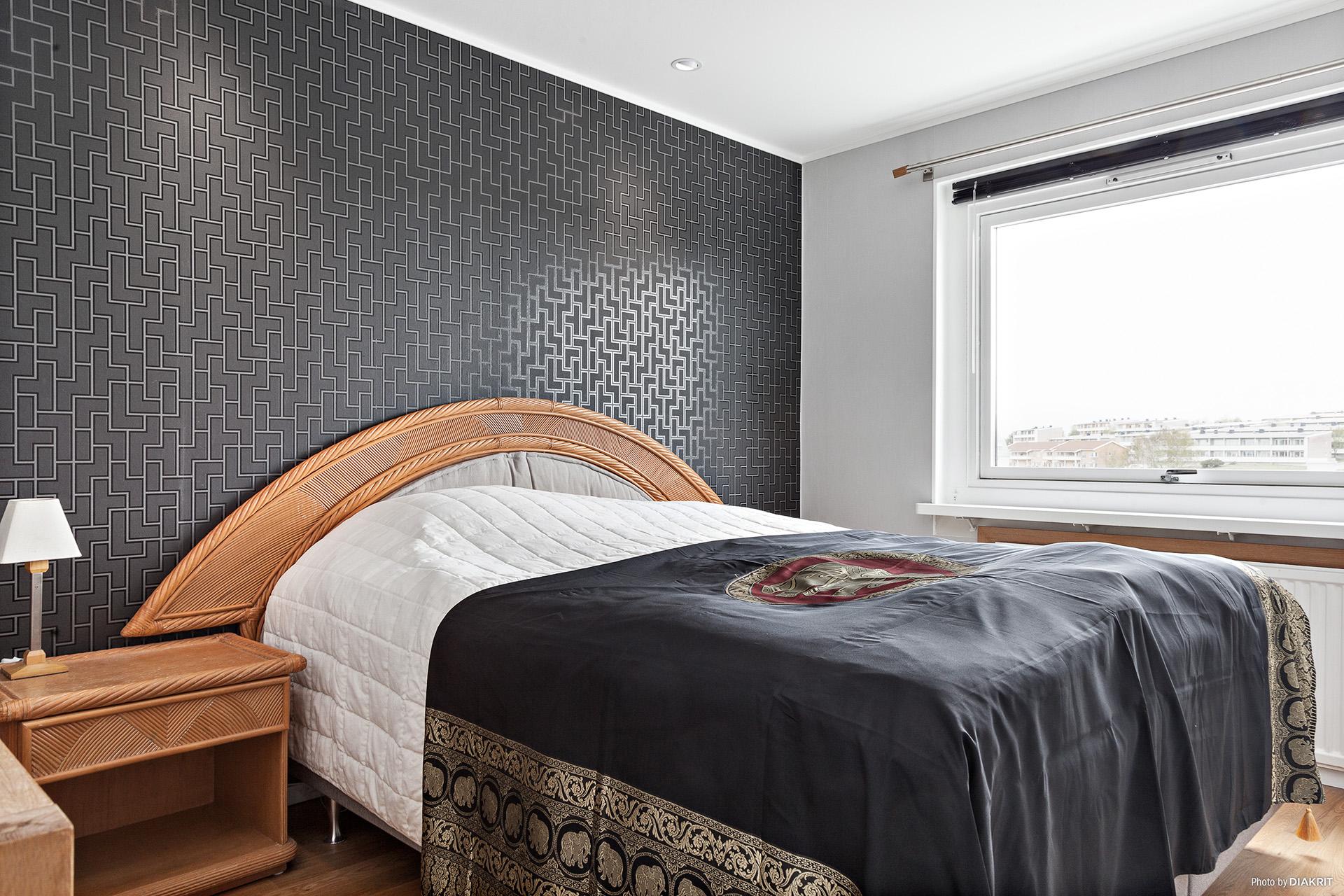Stiligt sovrum med garderober och fin utsikt över staden.