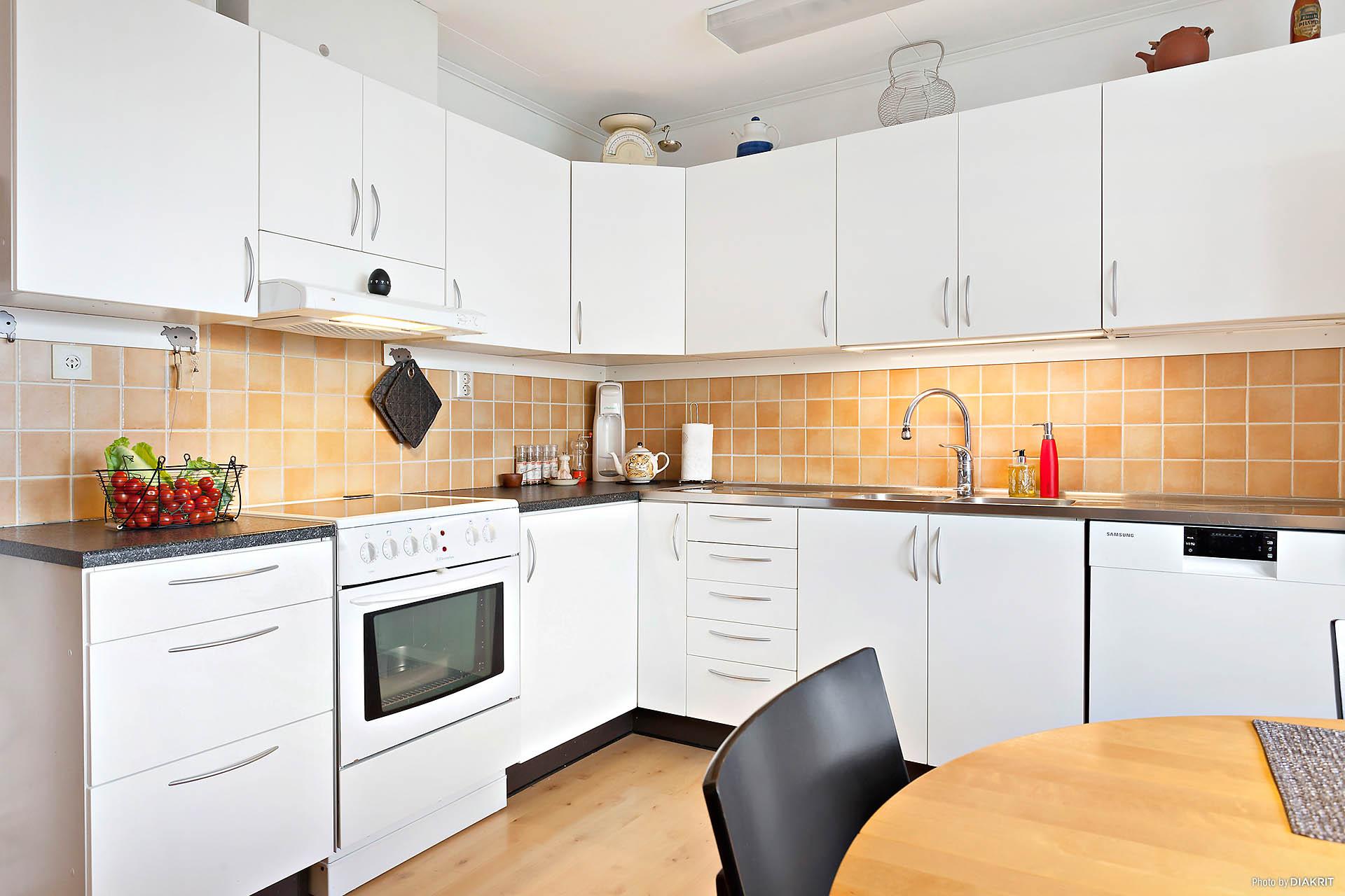 Hemtrevligt kök med plats för matbord framför fönstret