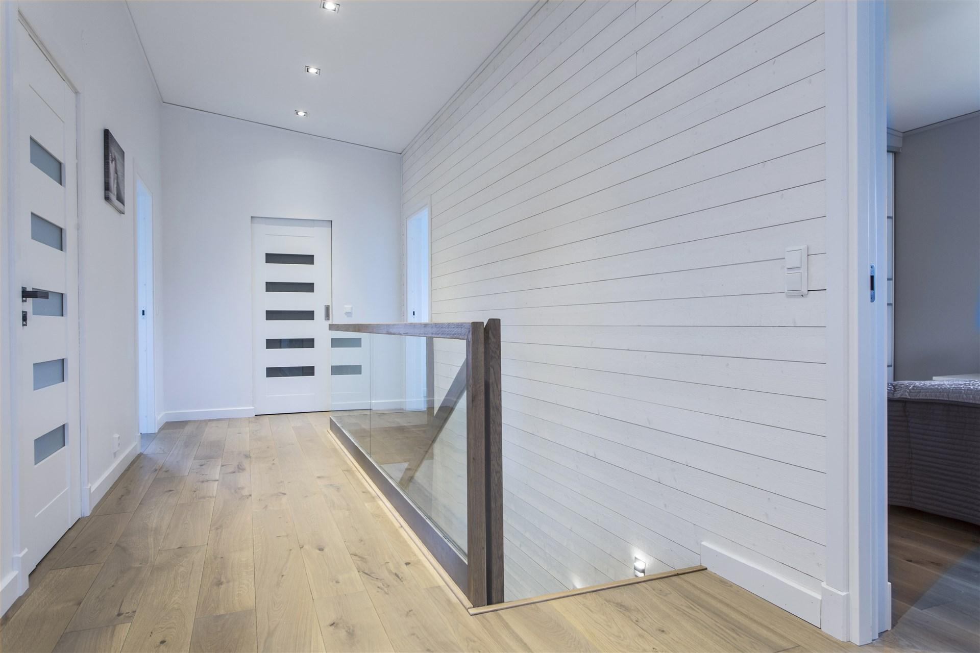 Luftig hall på övre plan med liggande panel.