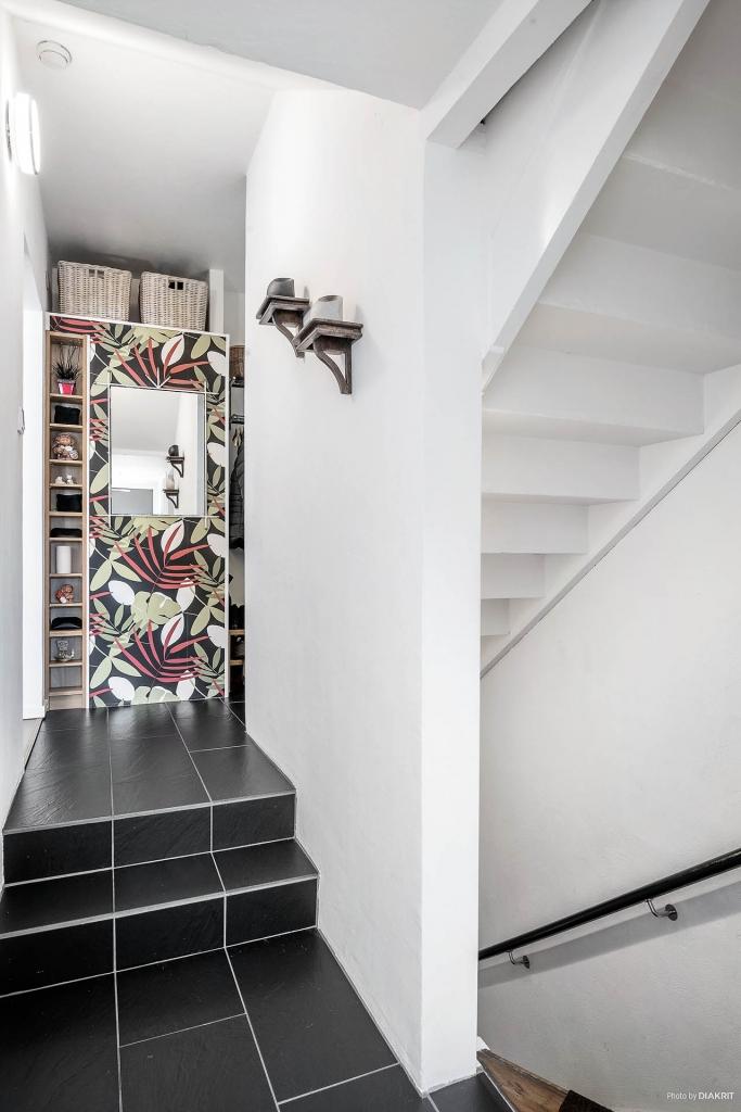 Hall mot vardagsrum till vänster och trappa till källare och ovanvåning till höger