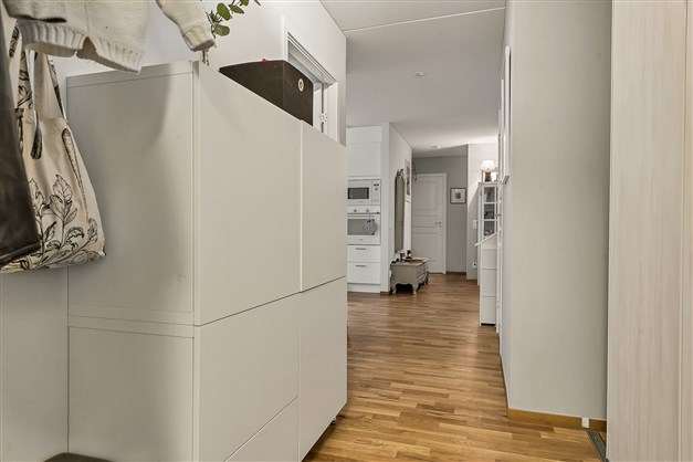 Rymlig hall med garderob bakom skjutdörrar samt plats för byrå