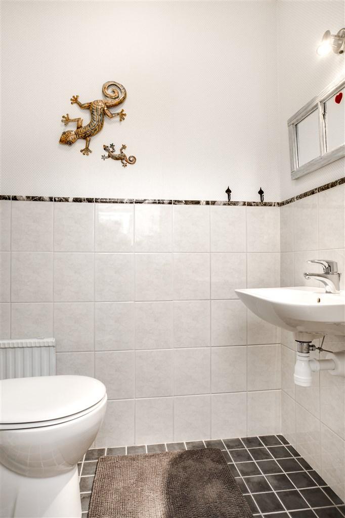 WC med klinker på golv och kakel/tapet på vägg.