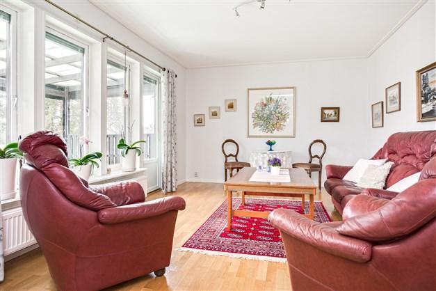 Ljust vardagsrum med uppgång till övervåningen och utgång till altan under tak.