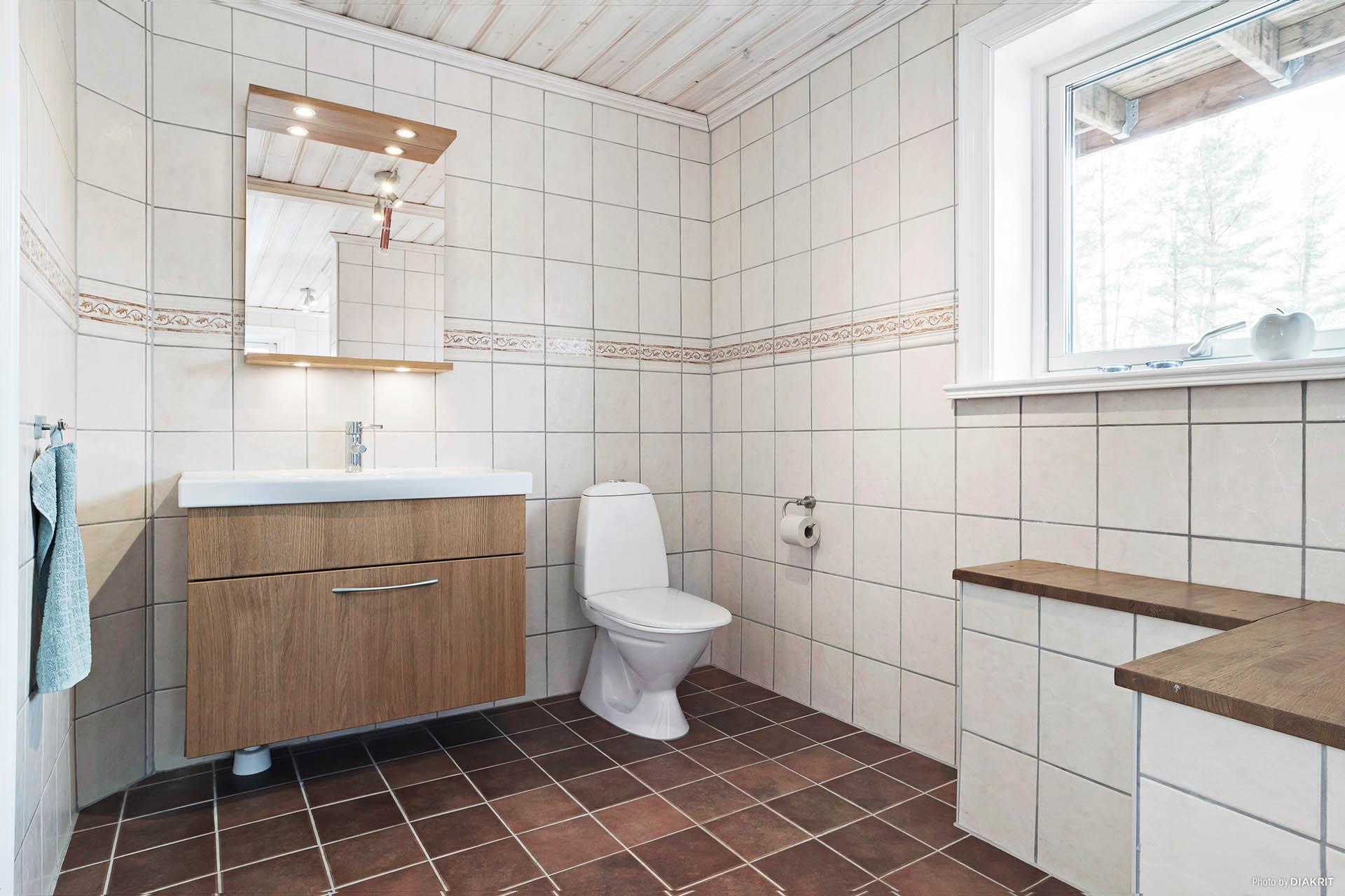 Helkaklad toalett med kommod i tvättstugan