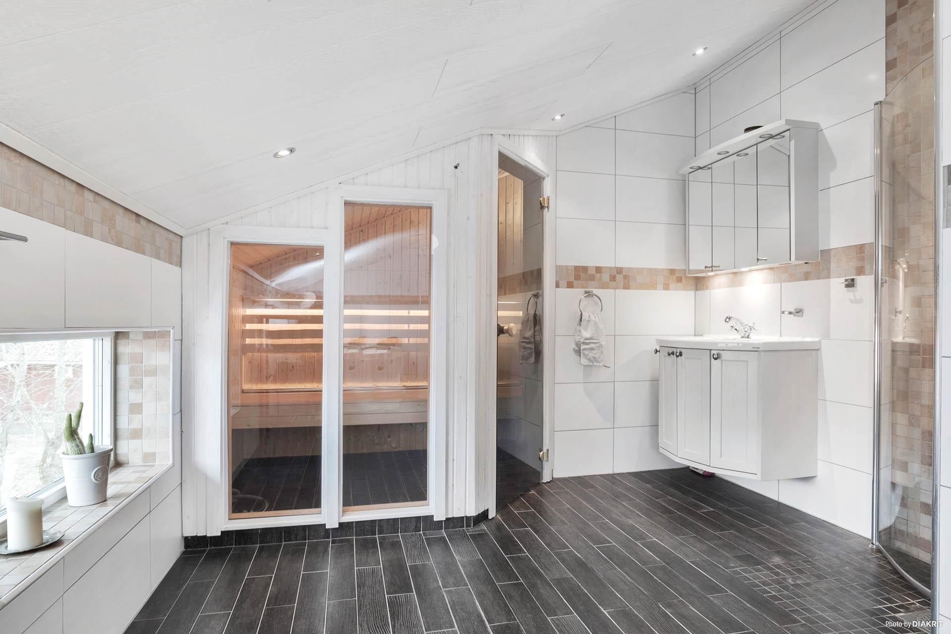 Elegant, rymligt och helkaklat badrum med bastu, dusch och bubbelbadkar.