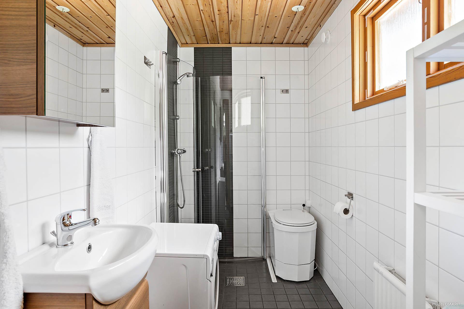 Helkaklat duschrum med förbränningstoalett och fönster