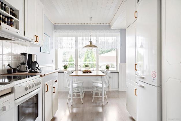 Praktiskt kök i ljusa färger. Här finns det gott om förvaring och arbetsytor.