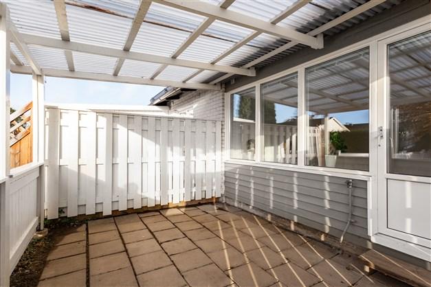 Altan under tak med nytt staket trädgårdsplattor.