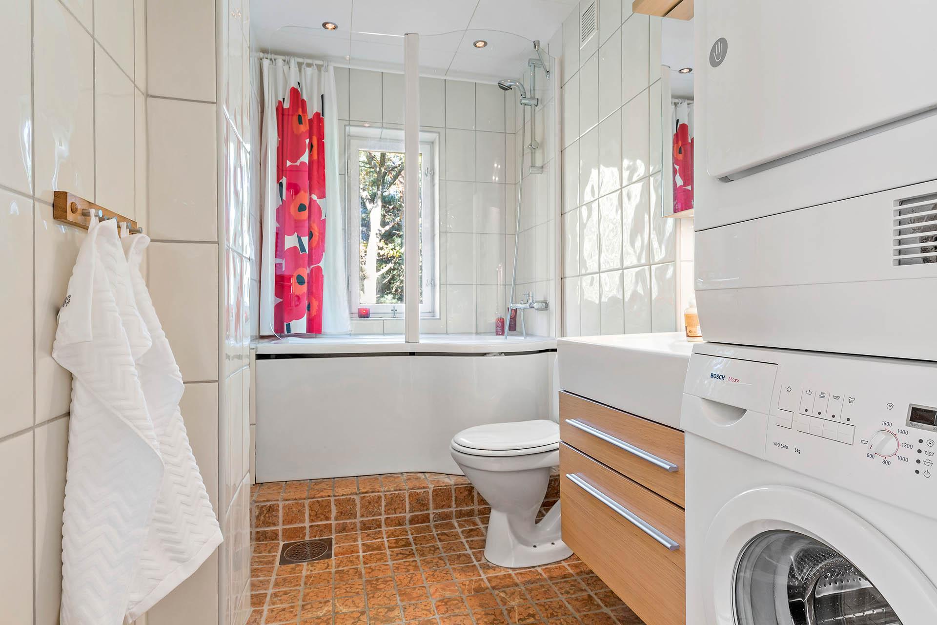 Helkaklat badrum med golvvärme och badkar.