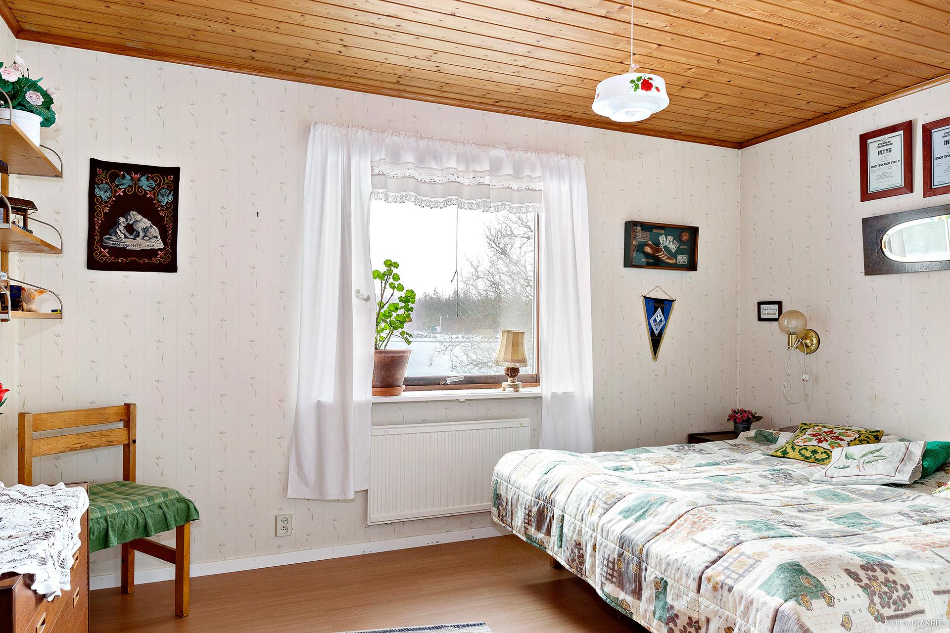 Ett av sovrummen med fönster mot husets framsida.