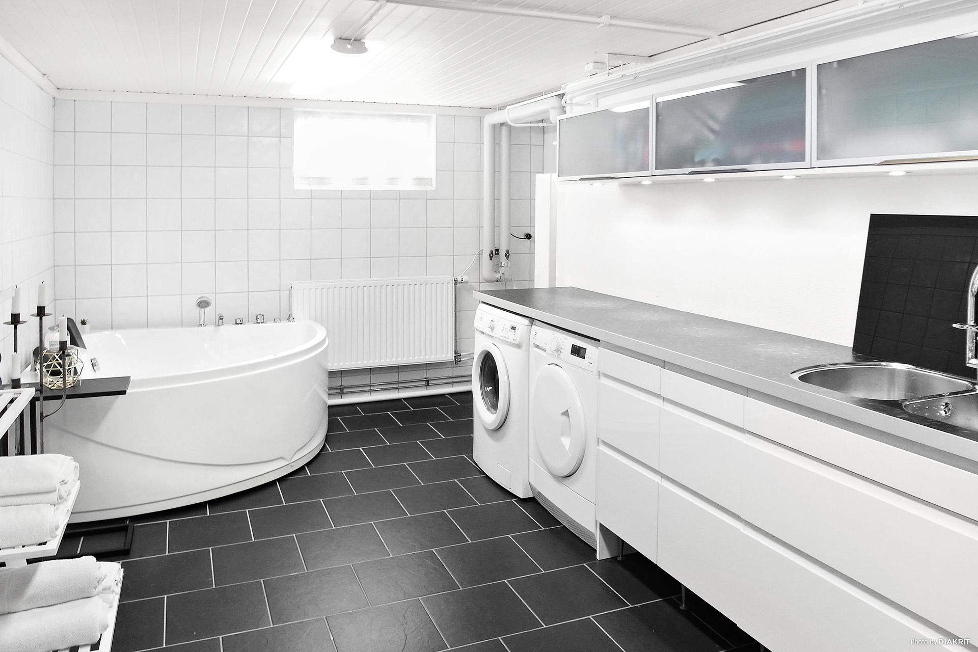 Stor ljus tvättstuga med inredning och bubbelbadkar!