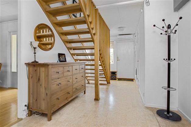 Ljus och rymlig hall med uppgång till övervåningen.
