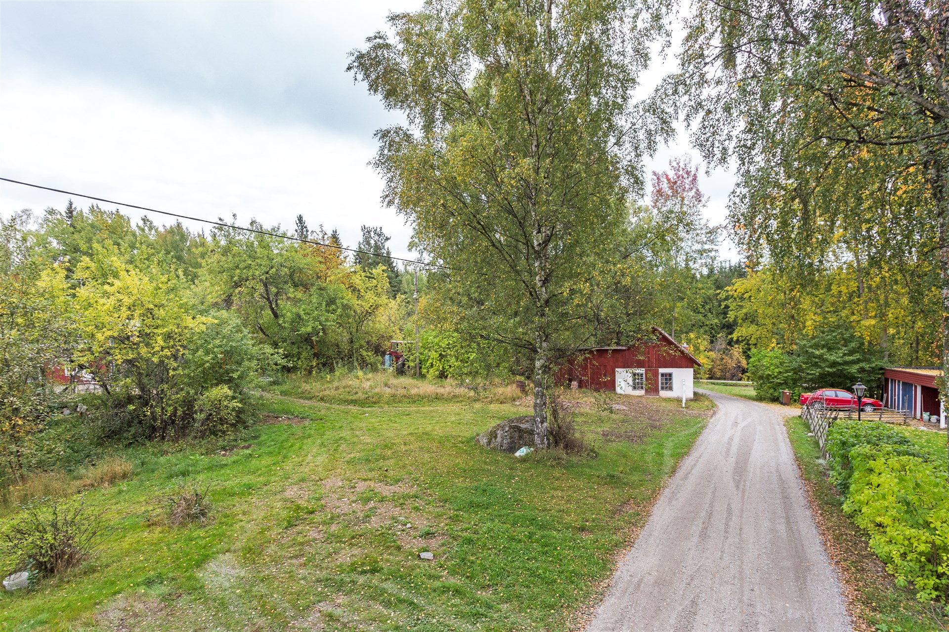 Gräsyta intill huset fungerar som parkering. Uthuset hör till huset.