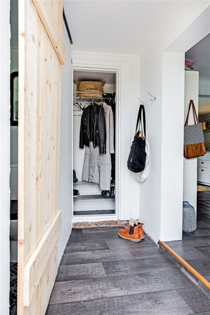 Välkommen in! Hall med praktiskt utrymme för kläder. Skjutdörr i trä till dusch/wc.
