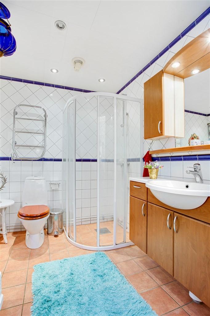 Badrum med klinker och golvvärme. Här finns både duschkabin och badkar med tassar.