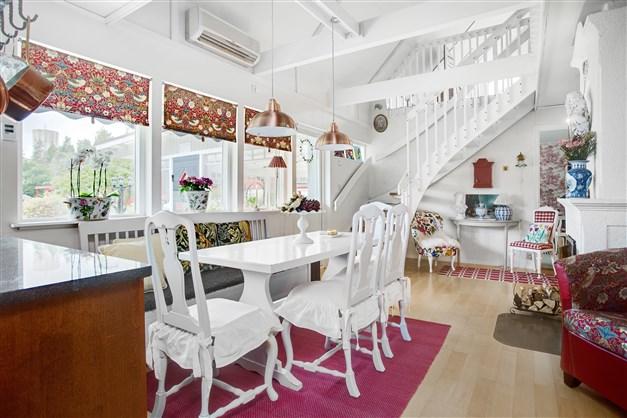 Matplatsen i matdelen och utgång till inglasad altan. Här finns en fin kakelugn. Trappa till övervåningen.