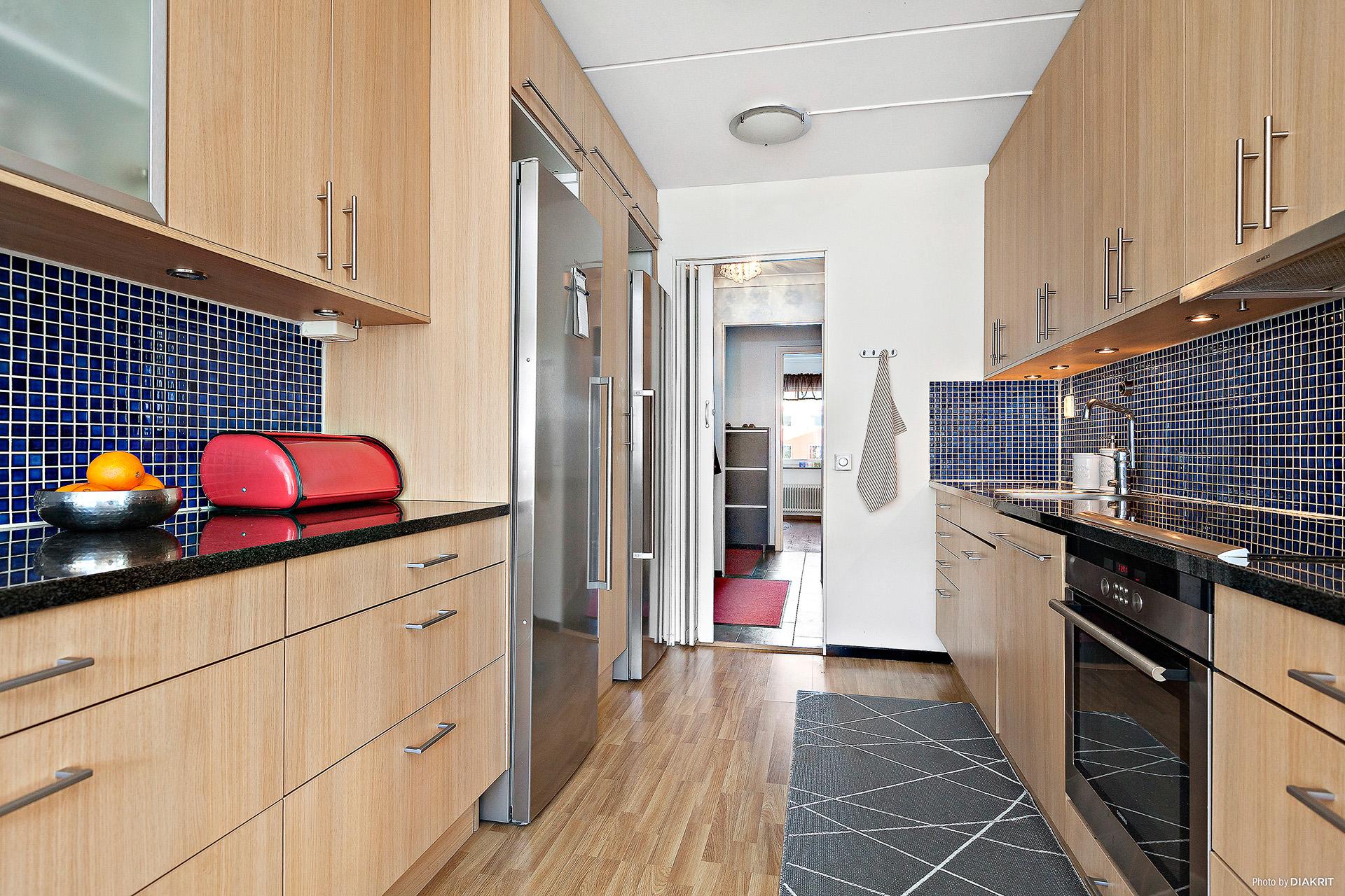 Kök i ljus ek med granitskivor och rostfria vitvaror.