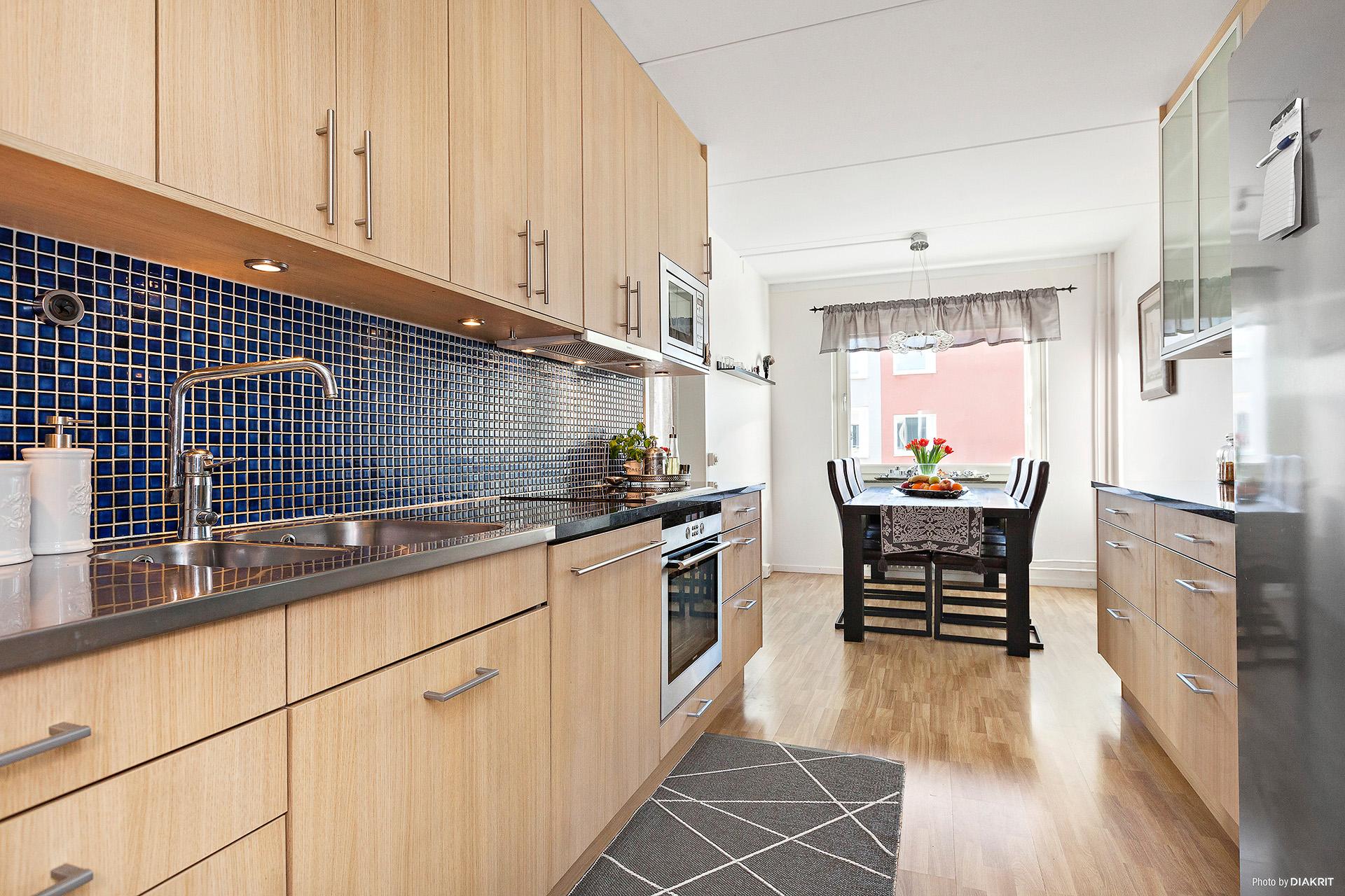 Köket med matplats invid fönster och öppning in till vardagsrummet.
