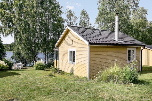 Fritidshuset i förgrunden med vy över trädgård med sjön i bakgrunden
