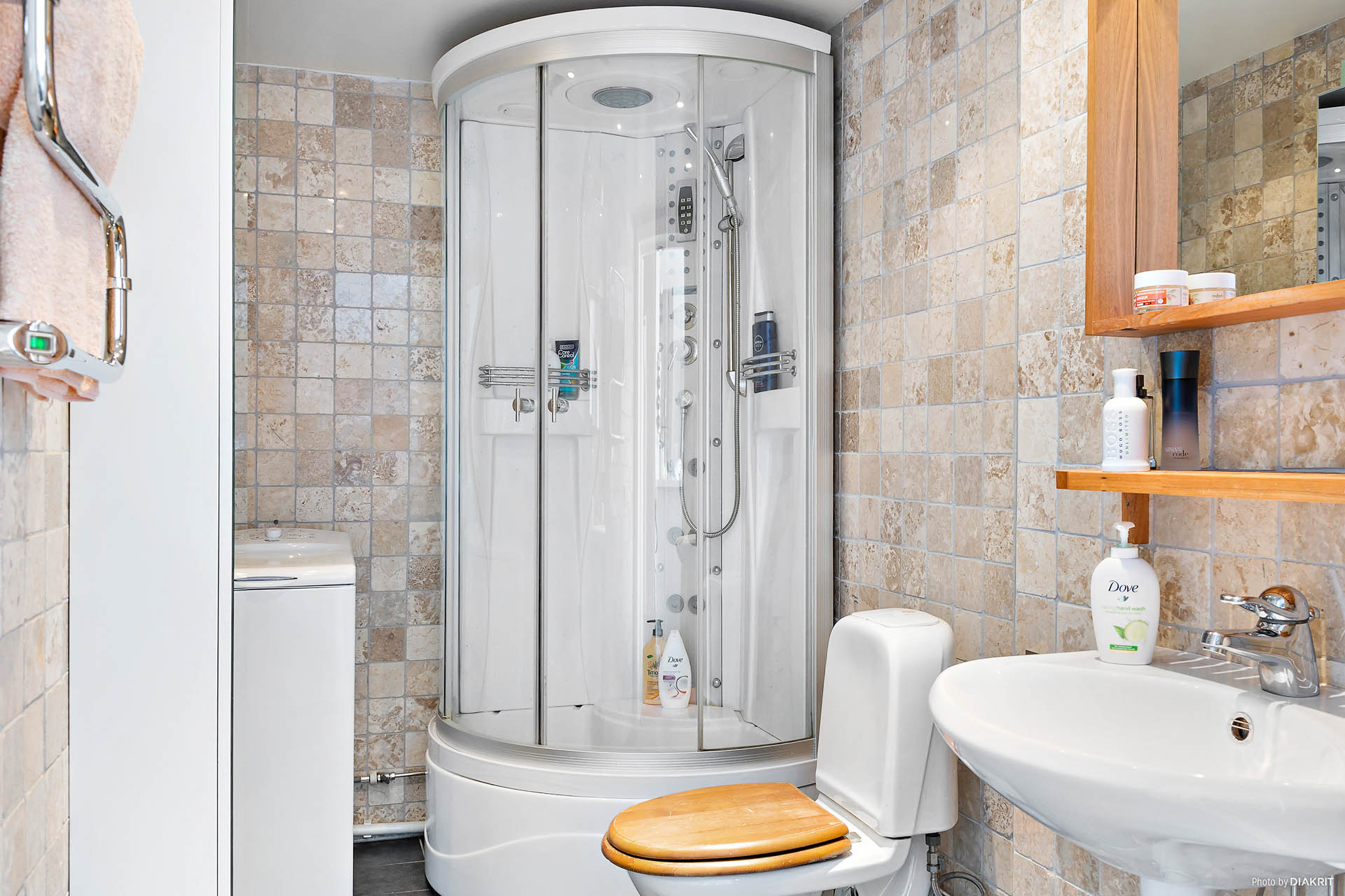Stort helkaklat duschrum med golvvärme och tvättmaskin.