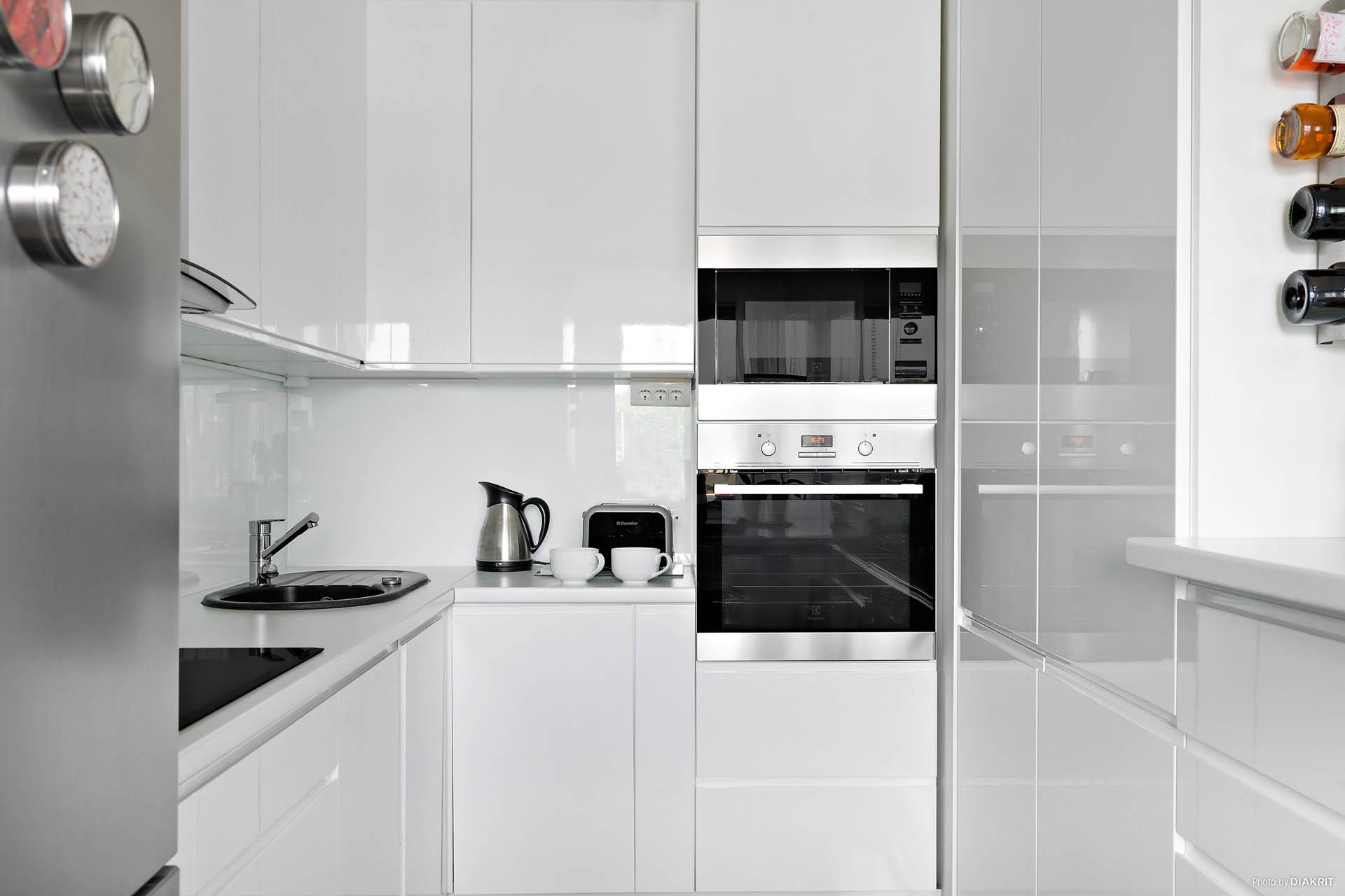 Totalrenoverat kök med marmorgolv och integrerade vitvaror.