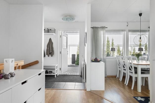 Hall och kök i en öppen planlösning.