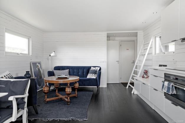Det svarta golvet är en fin detalj mot dem vitmålade väggarna och det vita köket.