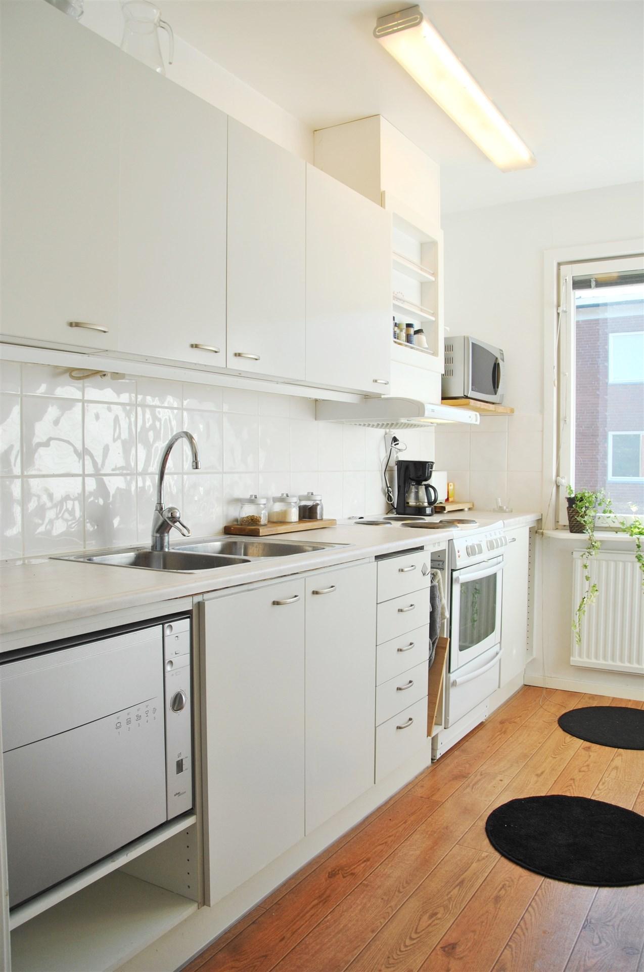 Kök med vita släta luckor och kakel över köksbänk