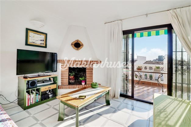 Vardagsrum med öppen spis och utgång till solig terrass