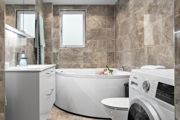 Badrum med tvättmaskin och massagebadkar