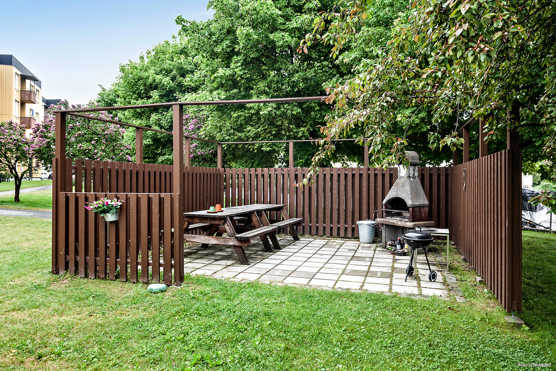 Gemensam uteplats med trädgårdsmöbler och grill