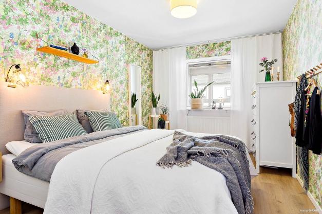 Rymligt sovrum med designad, blommig tapet.