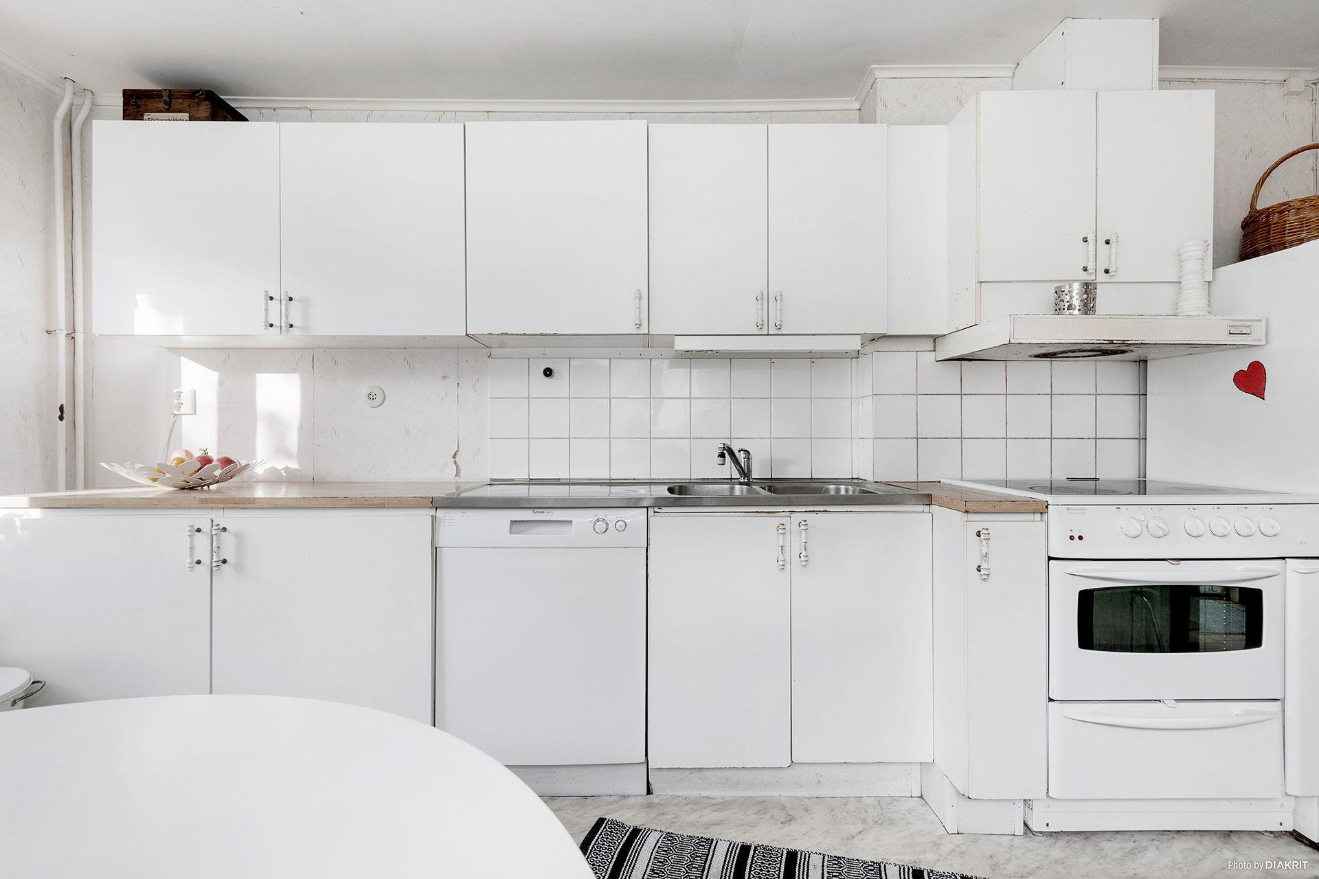 Vitt kök med släta luckor.