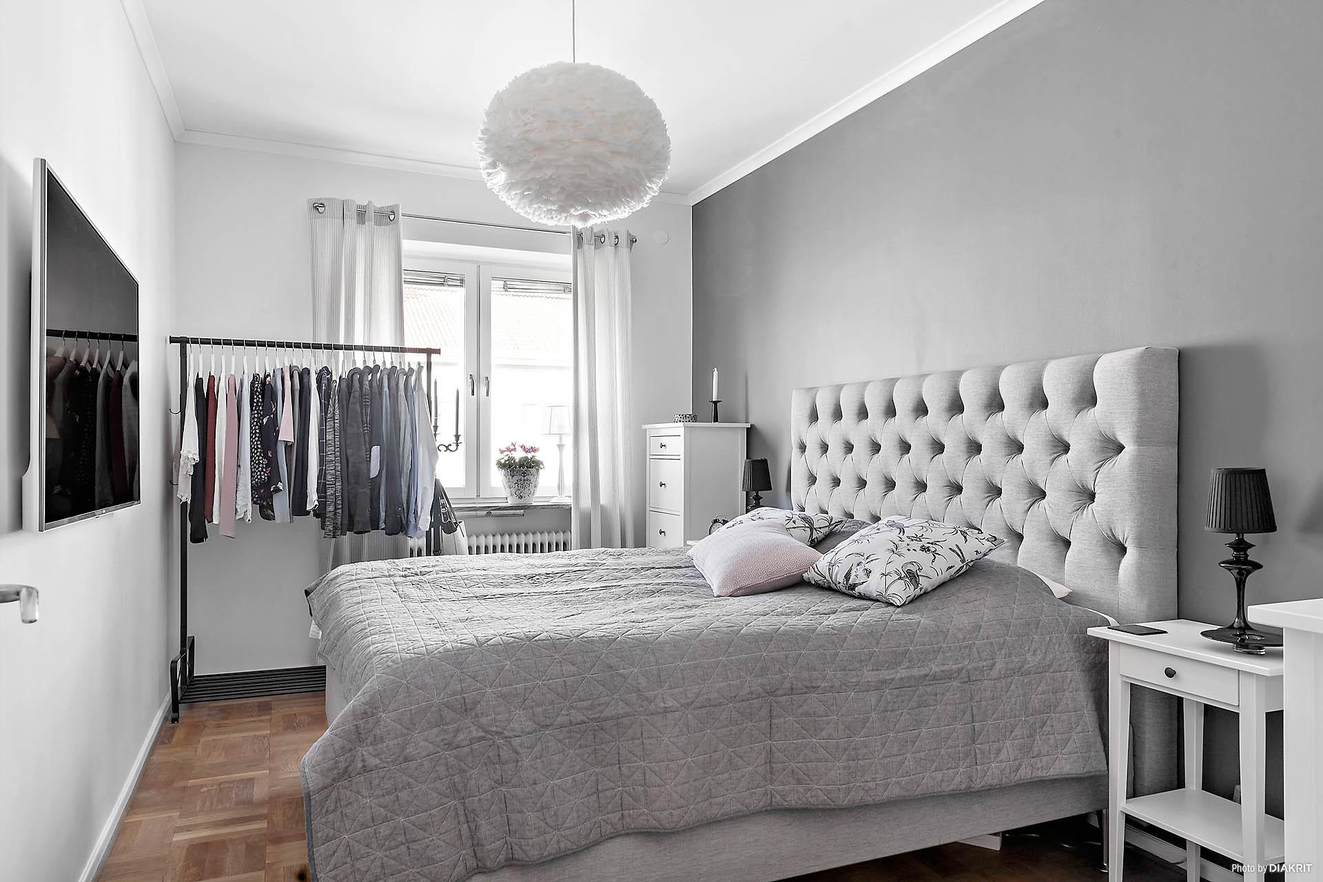 Sovrummet. Ett vilsamt rum med snygg grå nyans på ena väggen.