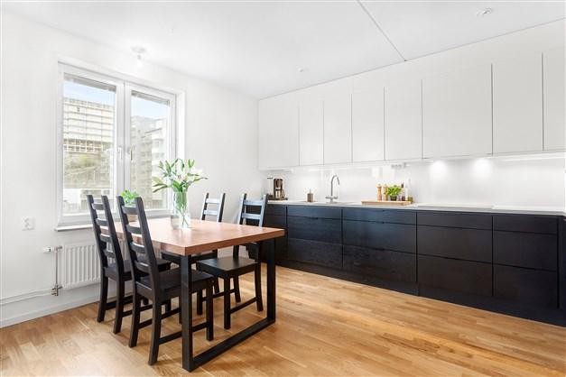 Stort kök i delvis öppen planlösning med vardagsrum.