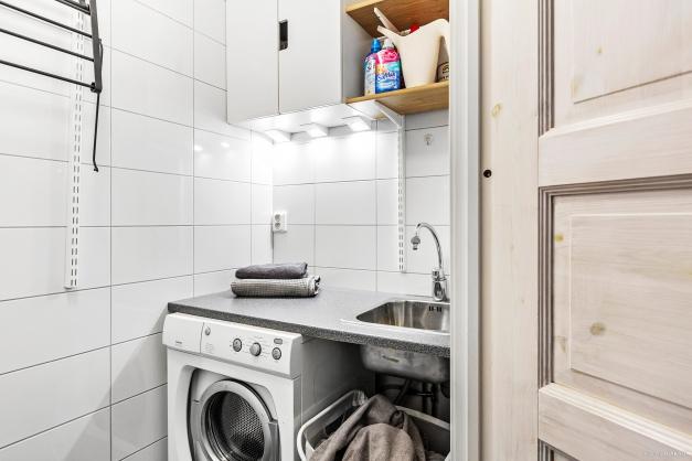 Praktisk tvättstuga inredd med tvättmaskin, bra arbetsbänk samt diskho.