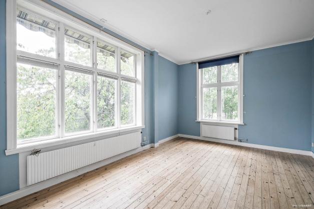 Sovrum med ståtliga fönsterpartier i lägenhet på entréplan i huvudbyggnad