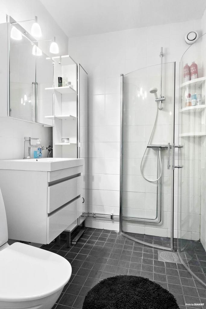 Riktigt fint badrum med kakel och klinker samt dusch, wc, handfat och skåp.