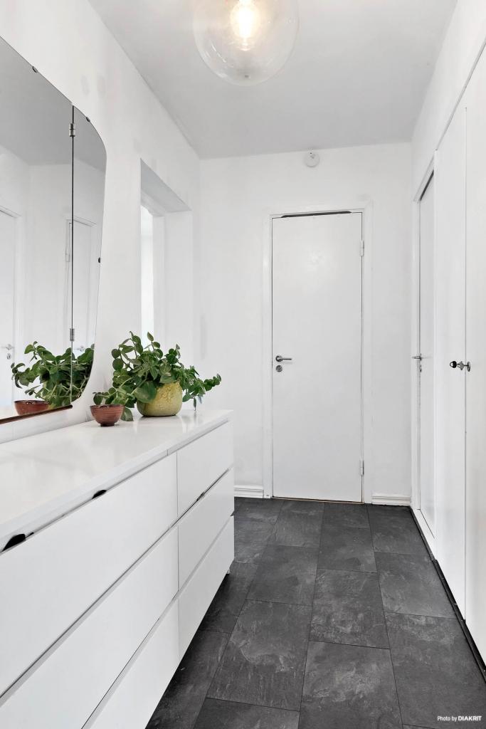 Grått laminatgolv i hallen och vitmålade väggar, här finns även två garderober