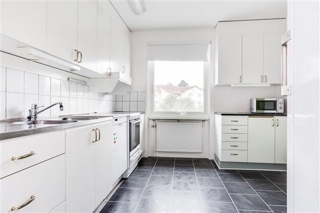 Kök med vit inredning och fönster ut mot gatan.